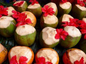 Frische grüne Kokosnüsse mit roten Blüten